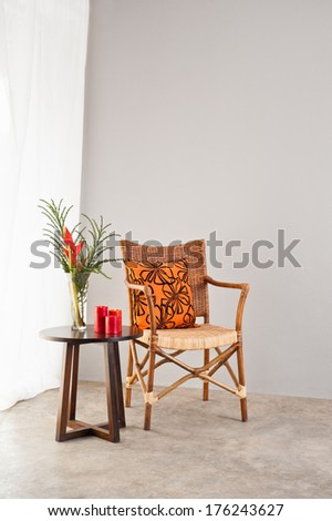 Rattan chair with orange colored pillow in a bright setting  - stock photo