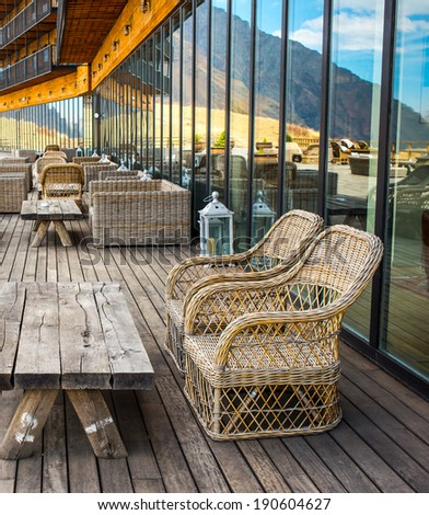 Rattan chairs and table on terrace in mountains - stock photo