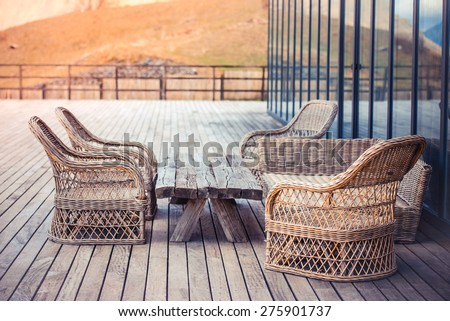 Rattan chairs and wooden table on terrace in mountains - stock photo