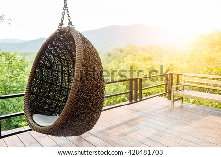 Rattan lounge hanging chair with white  pillow at the balcony with green nature background - stock photo