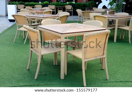Rattans dinner tables green yard - stock photo