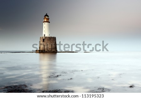 Rattray head lighthouse on the north east coast of Scotland as the Sun setting with the tide coming in - stock photo