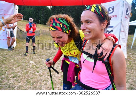 "rausor, romania - august 1, 2015: two women crossing the finish line at the trail running race ""retezat marathon""  in rausor, romania - retezat national park. shot taken on august 1st, 2015 - stock photo"