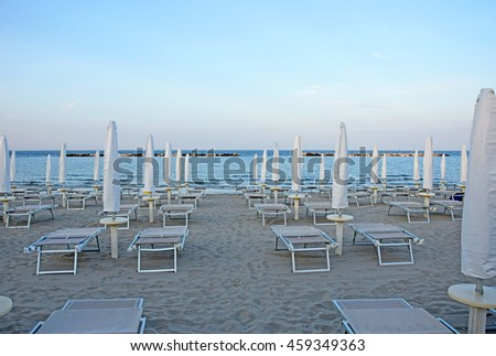 Ravenna, late afternoon at Adriano sand beach with umbrellas and deckchairs for summer vacations - stock photo