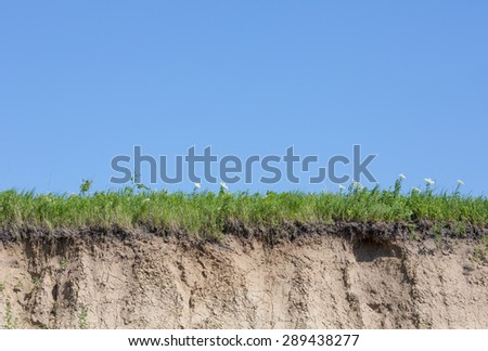 Ravine or gully cut with soil, grass and blue sky - stock photo