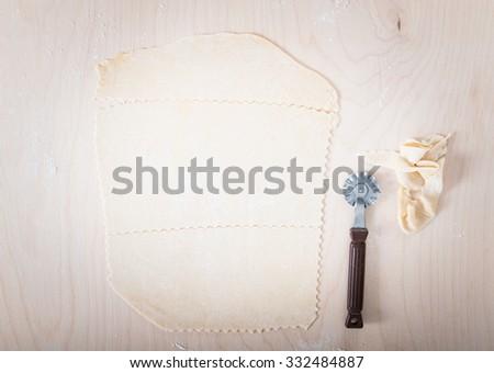 Ravioli and lasagna pastry sheet with cutting wheel. - stock photo