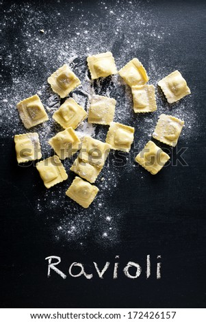 Ravioli pasta and flour on black background - stock photo