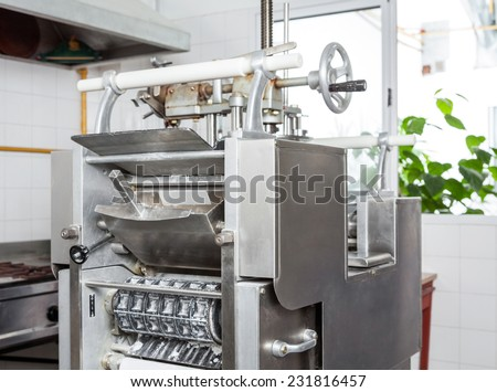 Ravioli pasta machine by window in commercial kitchen - stock photo