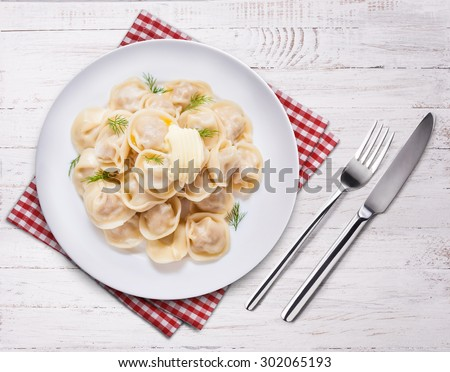 Ravioli pasta with sauce and fresh herbs. Top view on wooden table. Fork, knife and towel. - stock photo