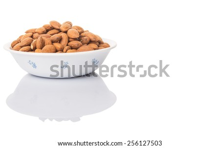 Raw almond nut in a white bowl over white background - stock photo