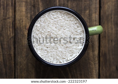 raw arborio rice in green pot on table, from above - stock photo