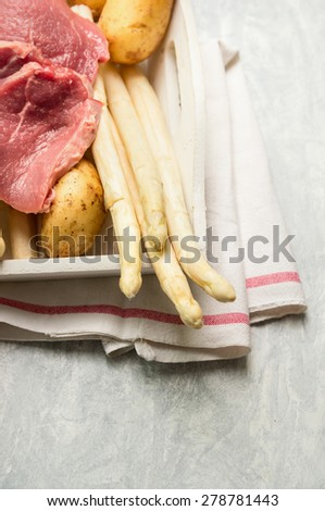 Raw asparagus with veal schnitzel and fresh potatoes - stock photo