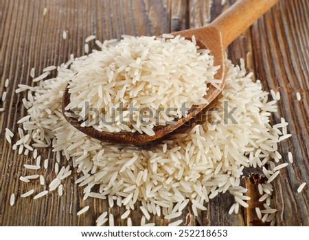 Raw basmati rice in  wooden  spoon . Selective focus - stock photo