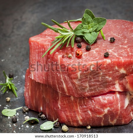 Raw beef fillet steaks with herbs and spices. - stock photo