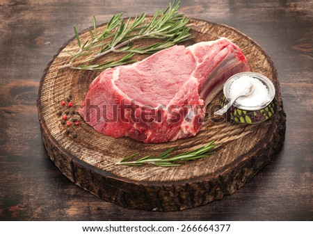 Raw beef meat on a wooden board - stock photo