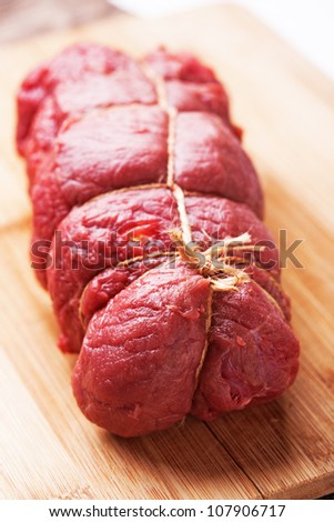 Raw beef meat tied with rope, ready to be cooked - stock photo