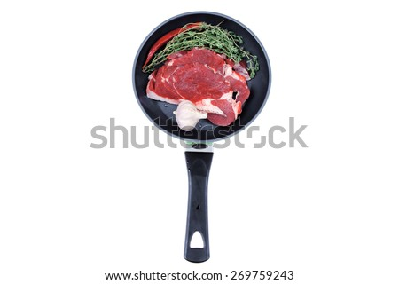 raw beef meat with thyme and pepper on black ceramic pan isolated on white background - stock photo