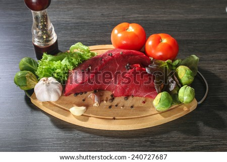 Raw beef meat with vegetables on wooden table close up - stock photo