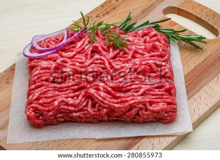 Raw beef minced meat with rosemary and onion - stock photo