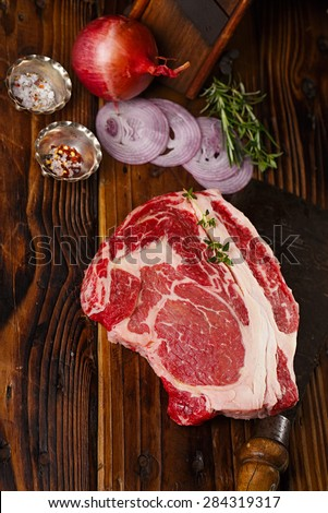 raw beef Ribeye  steak   on wooden  table with vintage butcher cleaver knife and spices - stock photo