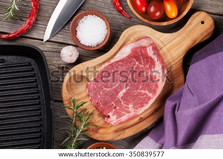 Raw beef steak and spices on wooden table. Top view - stock photo
