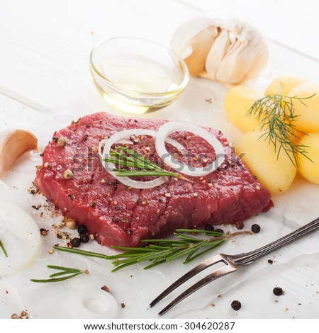 Raw beef steak and spices over white.  Healthy food concept. Selective focus. - stock photo