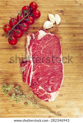 Raw beef steak on a dark wooden table with tomato,oregano and onion garlic - stock photo