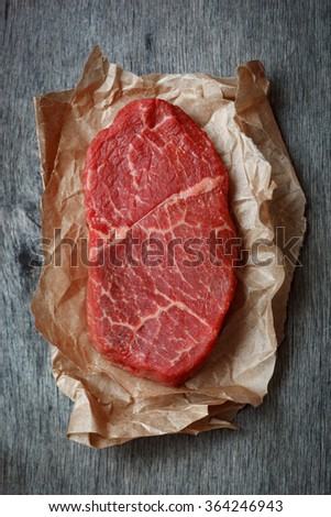 Raw beef steak on a paper - stock photo