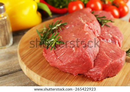 Raw beef steak on cutting board with vegetables and greens on wooden background - stock photo
