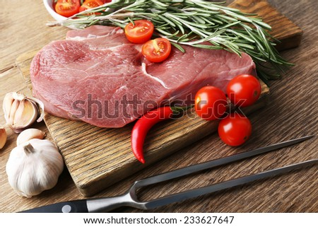 Raw beef steak on wooden table - stock photo