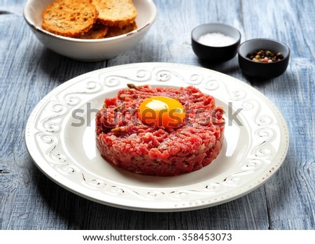 raw beef steak tartare with egg yolk, red onion, capers, spicy sauce, sea salt, pepper and olive oil. - stock photo