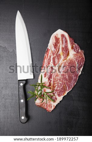Raw beef steak with rosemary and chef knife on dark wooden background - stock photo