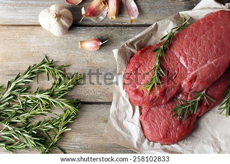 Raw beef steak with rosemary and garlic on paper on wooden background - stock photo