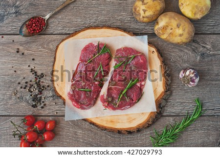 Raw beef steak with spices, herbs and ingredients on wooden table - stock photo