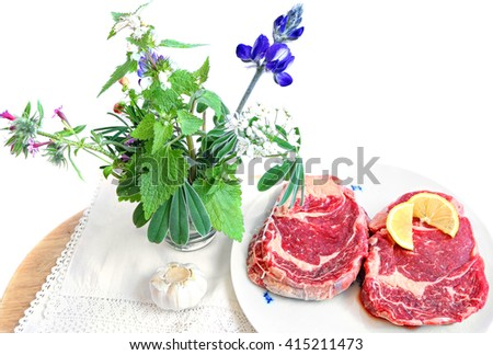 Raw beef steak with spices (sliced lemon and garlic) ready for cooking.Wild herbs and flowers on the wood board with white linen cloth.Isolated on white.Food ingredients and herbs kitchen still life - stock photo