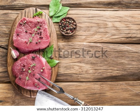 Raw beef steaks with spices on a wooden board. - stock photo