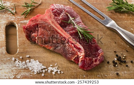 Raw beef t-bone steak on a wooden table. - stock photo