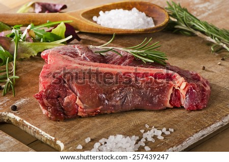 Raw beef t-bone steak on  old wooden table. - stock photo