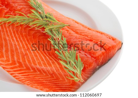 raw big salmon bar on white plate and rosemary - stock photo