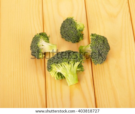 Raw broccoli and ripe on the background of light wood. - stock photo