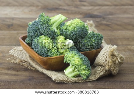 Raw broccoli in a bowl on wooden background - stock photo
