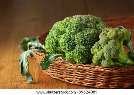 Raw broccoli in wicker basket on wooden surface. - stock photo