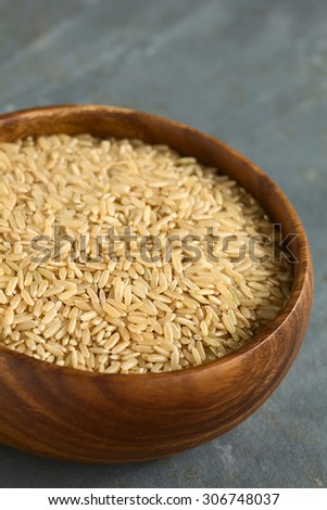 Raw brown or wholegrain rice kernels in wooden bowl, photographed on slate with natural light (Selective Focus, Focus one third into the rice) - stock photo