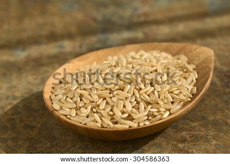 Raw brown or wholegrain rice kernels on small plate, photographed on slate with natural light (Selective Focus, Focus one third into the rice) - stock photo