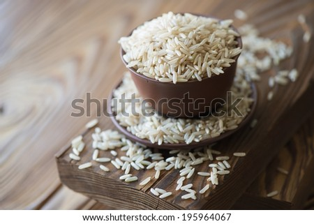 Raw brown rice in ceramic tableware over wooden background - stock photo