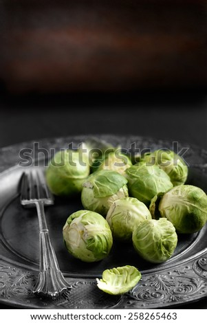 Raw brussel sproats in a rustic, farmhouse setting against a dark background. Differential focus and copy space. Ideal image for seasonal stories and blogs about sprouts at Christmas and Thanksgiving. - stock photo
