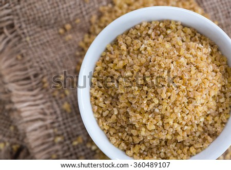 Raw Bulgur (on wooden background) as detailed close-up shot - stock photo