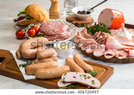 Raw burger with sausages, sliced ham and bacon  - stock photo