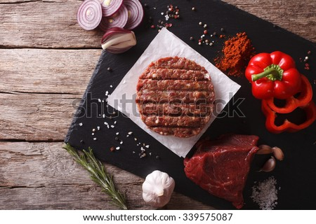 Raw burgers cutlets with the ingredients on the table. horizontal view from above - stock photo