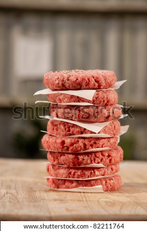 Raw burgers for hamburgers, in a pile in a garden - stock photo